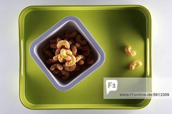 Erdnussflips auf grünem Plastiktablett Erdnussflips auf grünem Plastiktablett