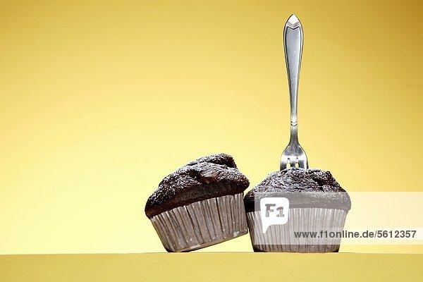 Zwei Schoko-Muffins mit Kuchengabel Zwei Schoko-Muffins mit Kuchengabel