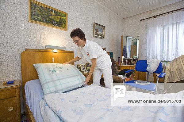 Ambulante Pflege des Deutschen Roten Kreuzes  Pflegeschwester Anke Lehmann macht das Bett für eine Herzinfarktpatientin  Treuenbrietzen  Brandenburg  Deutschland  Europa