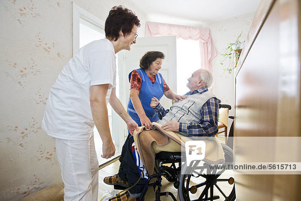 Ambulante Pflege des Deutschen Roten Kreuzes  Pflegeschwester Anke Lehmann besucht jeden Morgen ein altes Ehepaar und hilft der Ehefrau  den demenzerkrankten Ehemann vom Bett in den Rollstuhl zu heben  Niemegk  Brandenburg  Deutschland  Europa