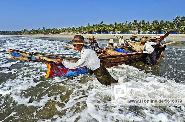 Fishermen entering the sea at the palm beach of Ngwe Saung Beach  Myanmar  Burma  Southeast Asia  Asia