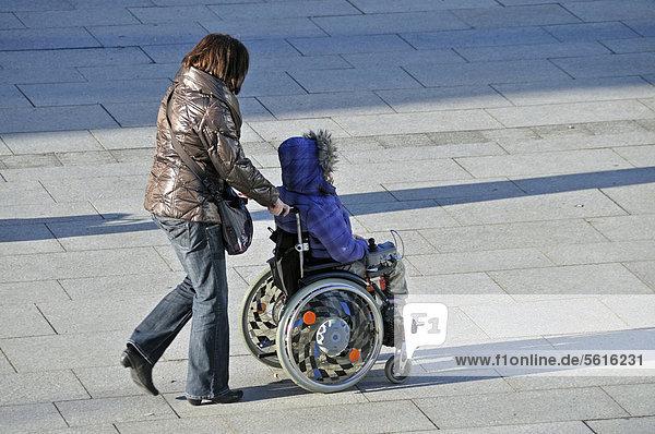 Frau im Rollstuhl wird geschoben  ÖffentlicherGrund