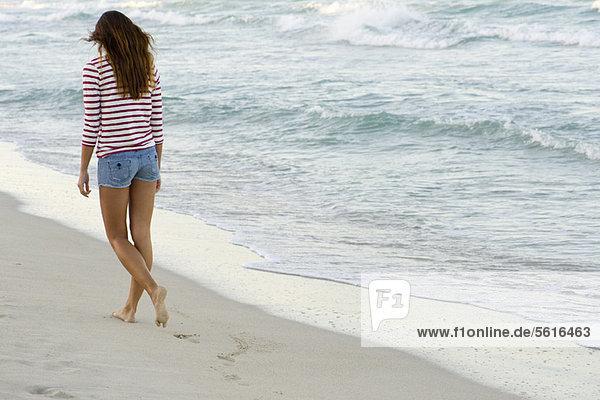 Frau beim Spaziergang am Strand  Rückansicht