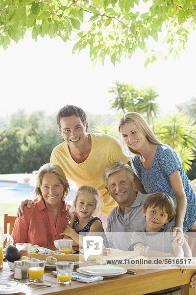 Mehrgenerationen-Familie am Frühstückstisch im Freien