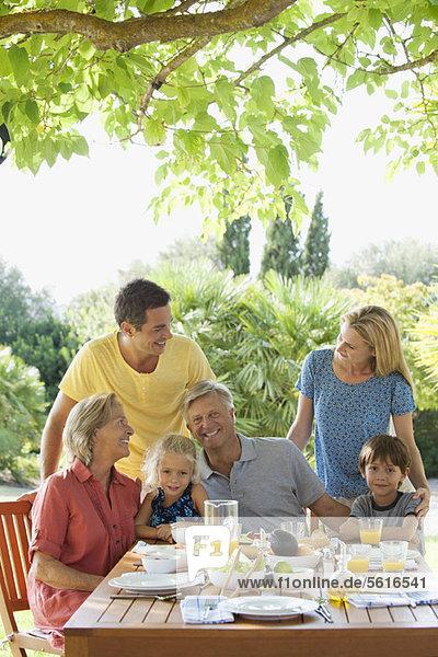 Mehrgenerationen-Familie beim Frühstück im Freien