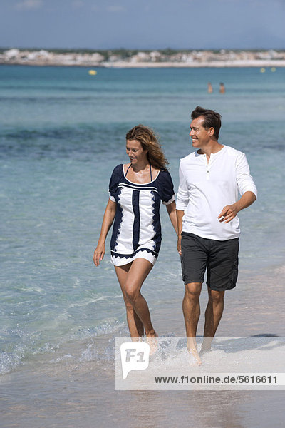 Couple walking on beach holding hands  ankles deep in water