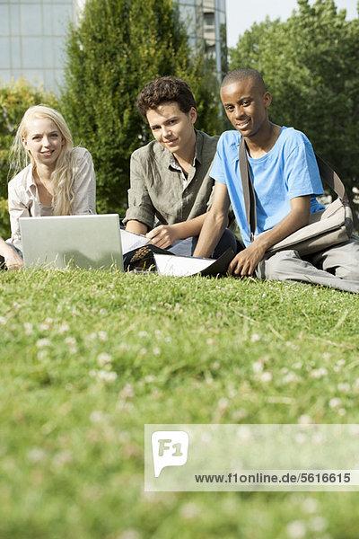 Universitätsstudenten  die gemeinsam auf Rasen studieren  Blickwinkel niedrig
