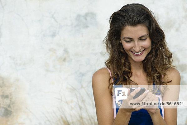 Junge Frau SMS mit Handy