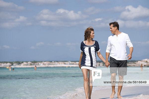 Paar  das am Strand läuft und Händchen hält  Porträt