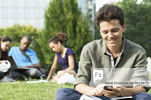 Junger Mann SMS mit Handy  Gruppe von Menschen im Hintergrund