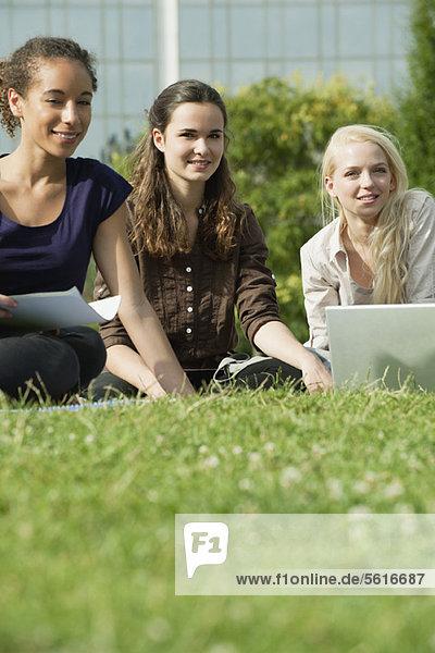 Studentinnen studieren gemeinsam auf Rasen  Blickwinkel niedrig