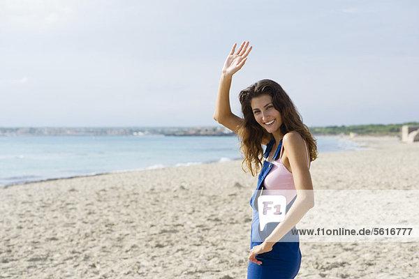 Junge Frau am Strand  lächelnd und winkend vor der Kamera