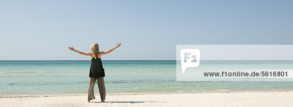Frau am Strand stehend mit ausgestreckten Armen  Rückansicht