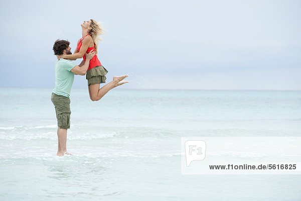 Paar am Strand  Mann hebt Frau in die Luft