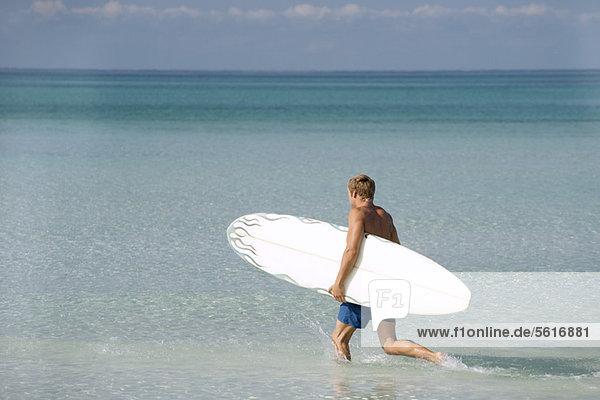 Mann mit Surfbrett im Wasser  Rückansicht