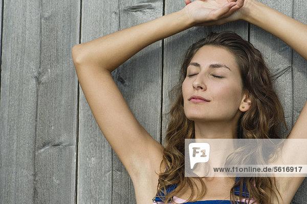 Junge Frau lehnt sich mit geschlossenen Augen an die Wand  Portrait