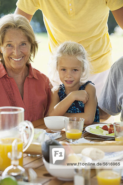Girl and grandmother at breakfast table outdoors  cropped