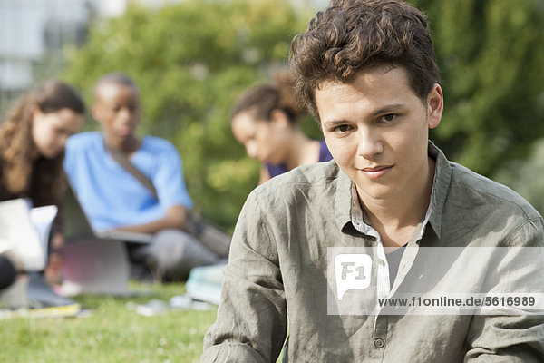 Young man outdoors  people in background  portrait