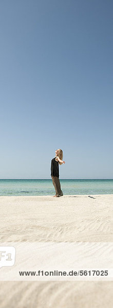 Frau am Strand stehend mit ausgestreckten Armen  Seitenansicht
