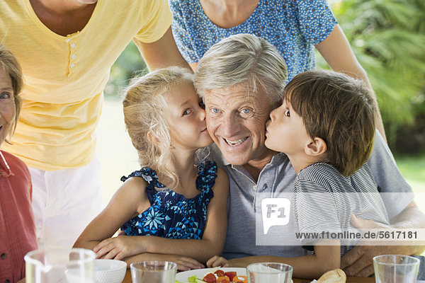 Enkelkinder küssen Großvater  Portrait