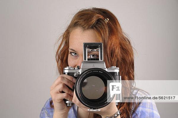 Junge Frau mit roten Haaren fotografiert mit einer analogen Mittelformatkamera Pentacon Six
