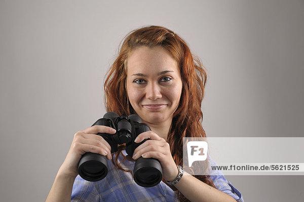 Junge Frau mit roten Haaren mit Fernglas in den Händen