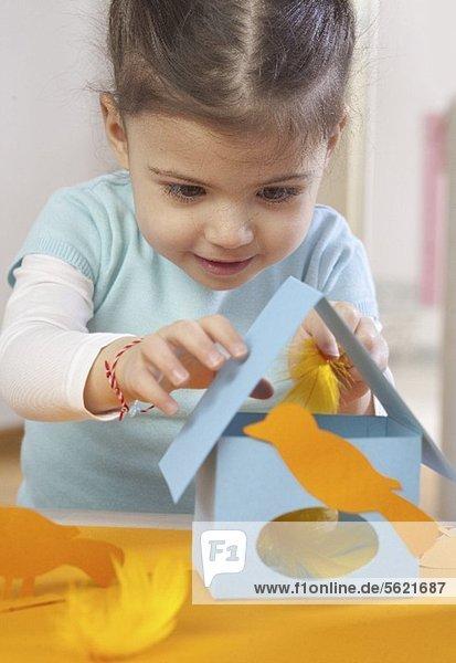 Kleines Mädchen bastelt Vogelhaus aus Papier