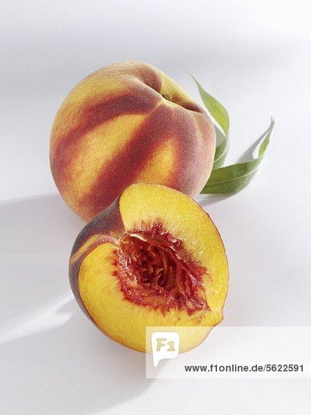 Ganzer und halber Pfirsich mit Blatt