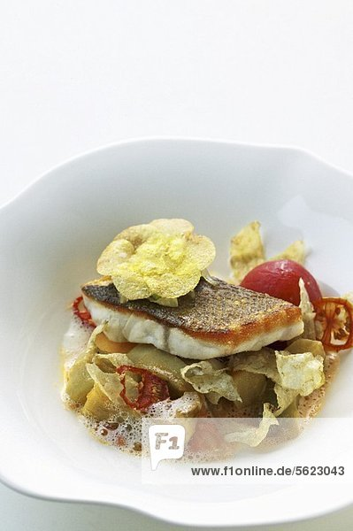 Bass with artichokes  tomatoes and braised onions