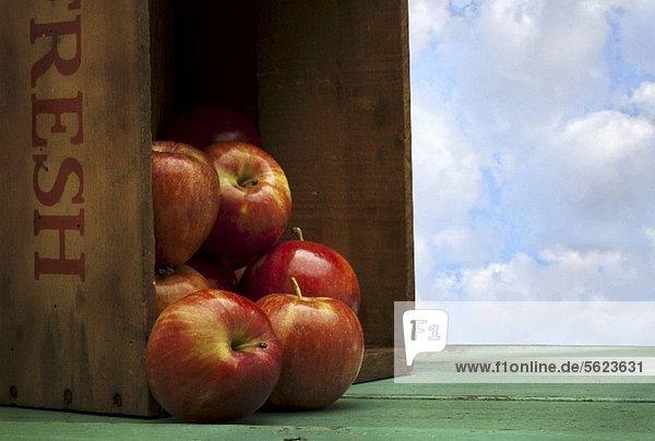 Frische Äpfel fallen aus einer Kiste