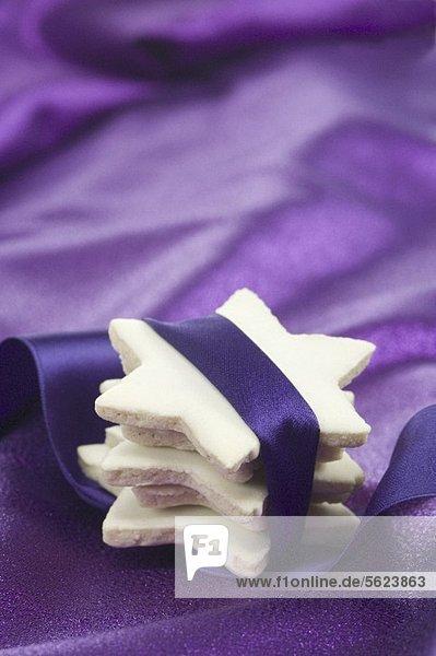 Gestapelte Zimtsterne in ein violettes Band gewickelt Gestapelte Zimtsterne in ein violettes Band gewickelt