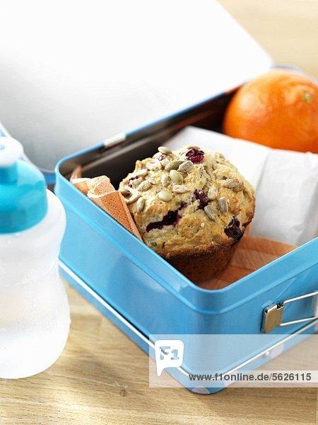 Lunchbox mit Cranberrymuffin und Orange