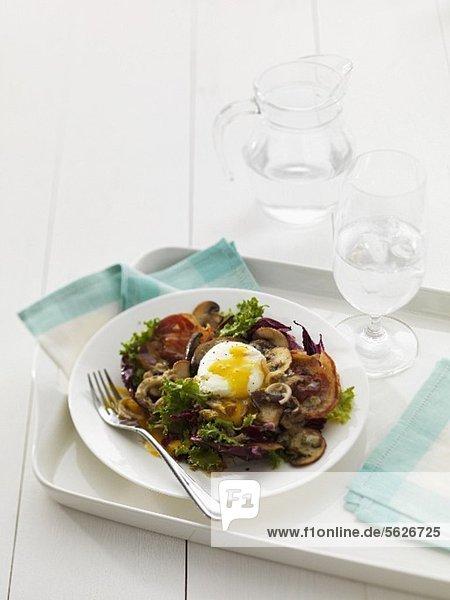 Blattsalat mit pochiertem Ei  Pilzen und Pancetta