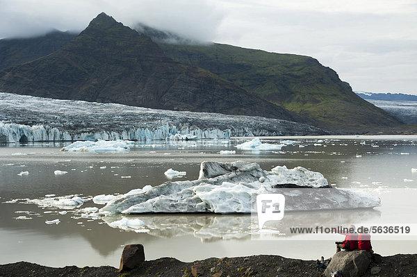 Ein Paar betrachtet von Asche schwarz gefärbte Eisberge und Gletscherzunge  Gletscherlagune Brei_·rlÛn  Breidarlon  Vatnajökull Gletscher  Austurland  Ost-Island  Island  Europa