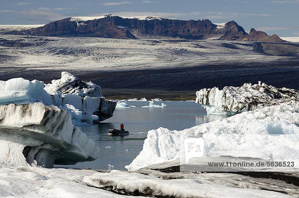 Schlauchboot oder Zodiac Boot  von Asche teils schwarz gefärbte Eisberge  Gletscherlagune Jökuls·rlÛn  Vatnajökull Gletscher  Austurland  Ost-Island  Island  Europa