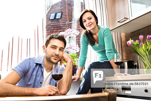 Junges Paar trinkt Rotwein in der Küche