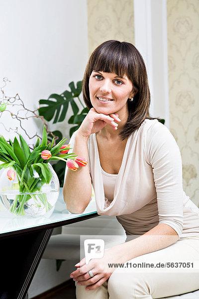 Junge Frau mit einem Strauß Tulpen zu Hause