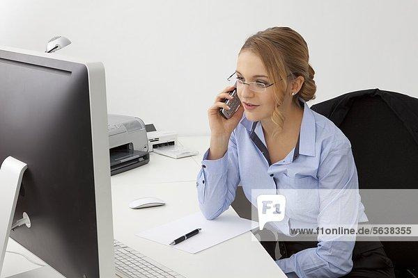 Junge Frau im Büro telefoniert