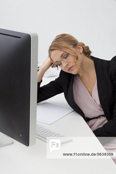 Junge Frau mit geschlossenen Augen am Schreibtisch