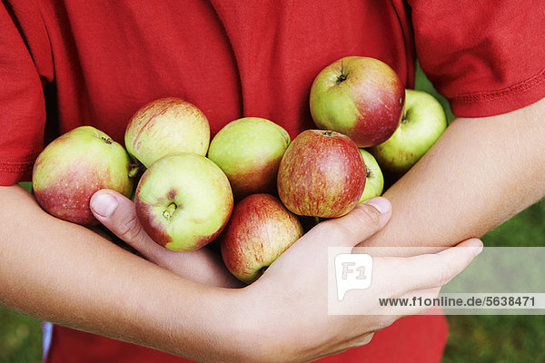 Kind mit einem Arm voller Früchte
