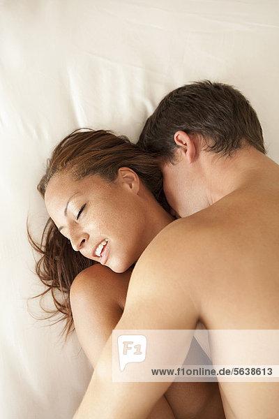 Nacktes Paar  das sich im Bett küsst