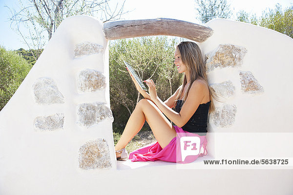 Woman using tablet computer outdoors