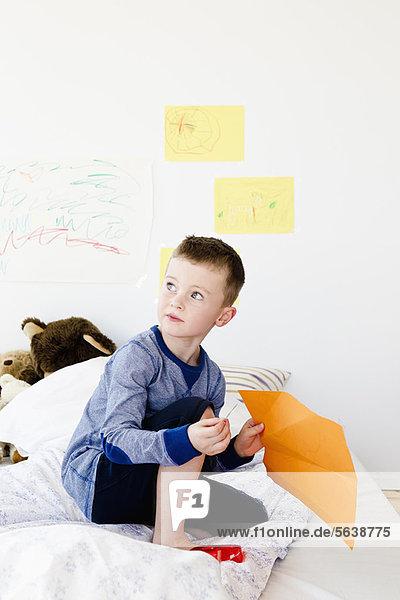 Junge hält Zeichnung auf Bett