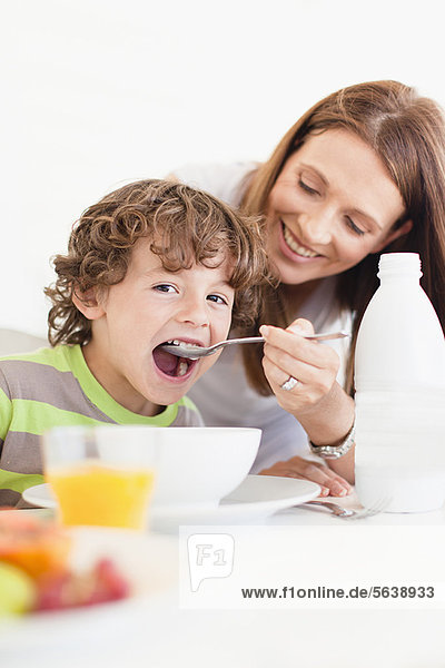 Mother feeding son cereal