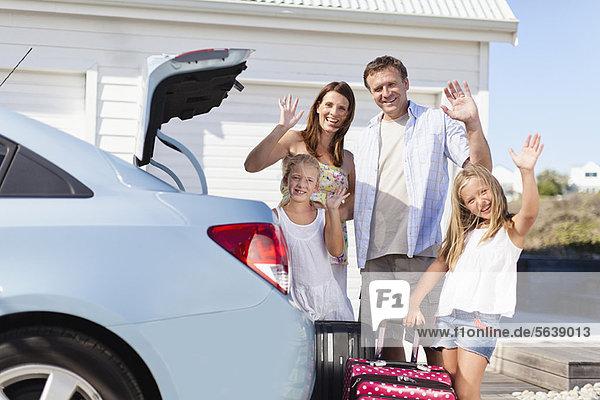Familie lädt den Kofferraum für den Urlaub auf