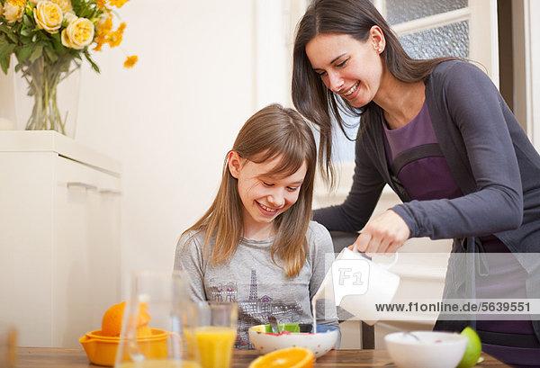Frau gießt Milch für die Tochter am Tisch