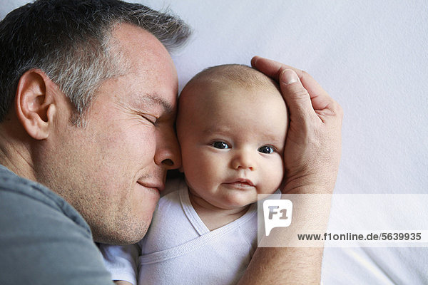 Vater wiegt Kleinkind im Bett