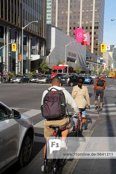 Autobahnkreuz  Städtisches Motiv  Städtische Motive  Straßenszene  Straßenszene  Frau  Mann  radfahren  Fahrradfahrer  Geschäftsviertel  Fahrrad  Rad  Kanada  Ontario  Toronto  Straßenverkehr