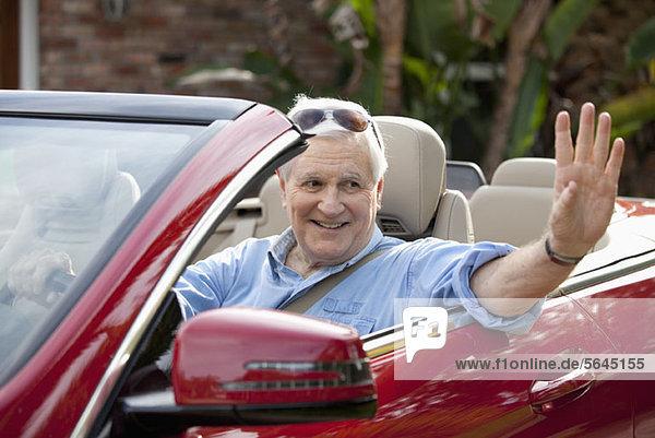 Ein älterer Mann  der vom Fahrersitz des Cabrios winkt.