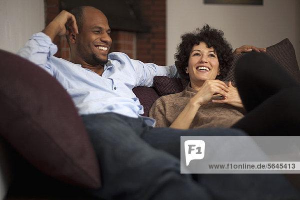 Ein lachendes Paar  das sich gemeinsam auf einem Sofa ausruht.